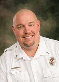 Brian Siekman Smiling man wearing white shirt with fire department badges