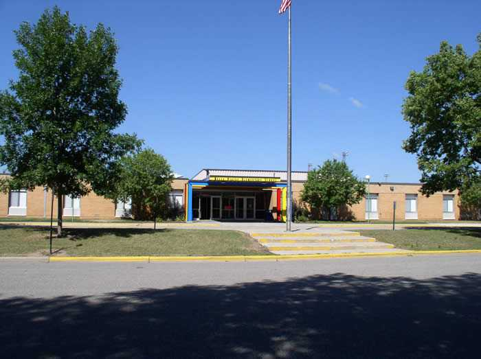 Chatfield Elementary School - one story brick building in the summer with leafy trees on each side