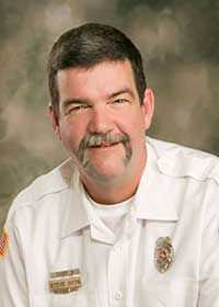Steve Otto Man with short hair wearing white shirt with fire department badges