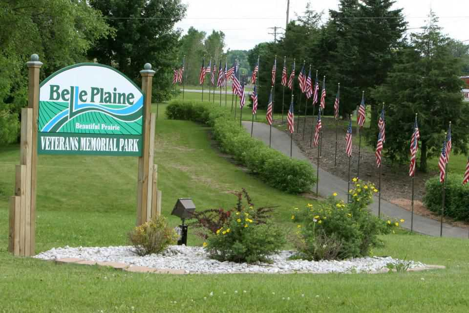 Green grass, trees and landscaping around City of Belle Plaine sign