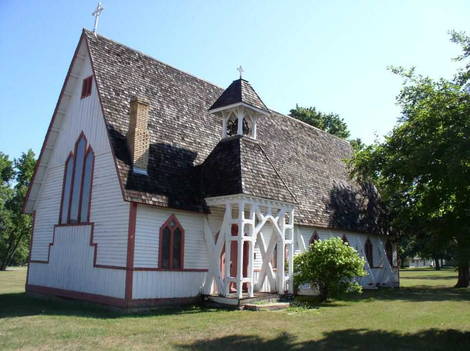 White church with grey shingles in summer